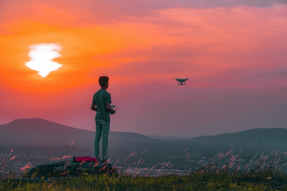 man in black jacket standing on green grass during sunset