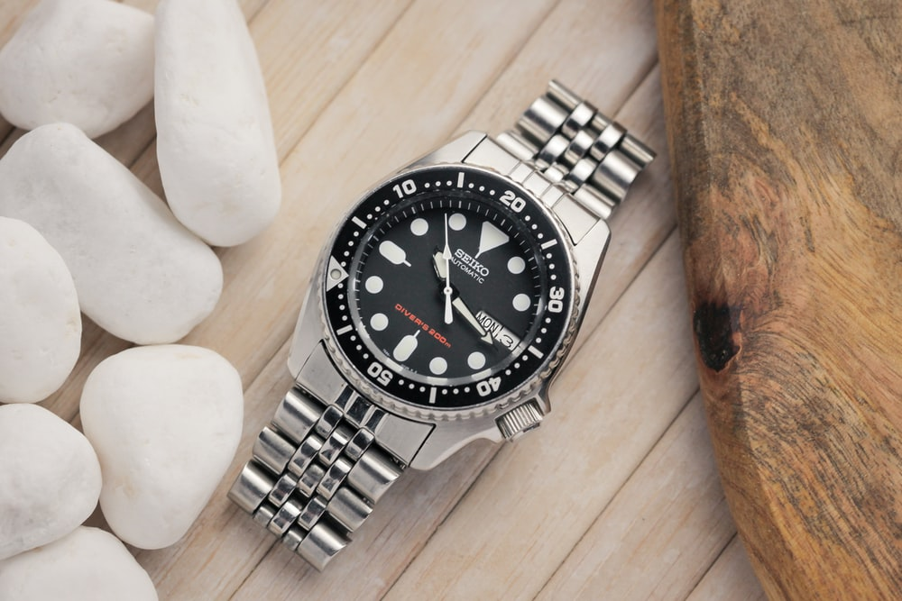 silver and black round analog watch at 10 10