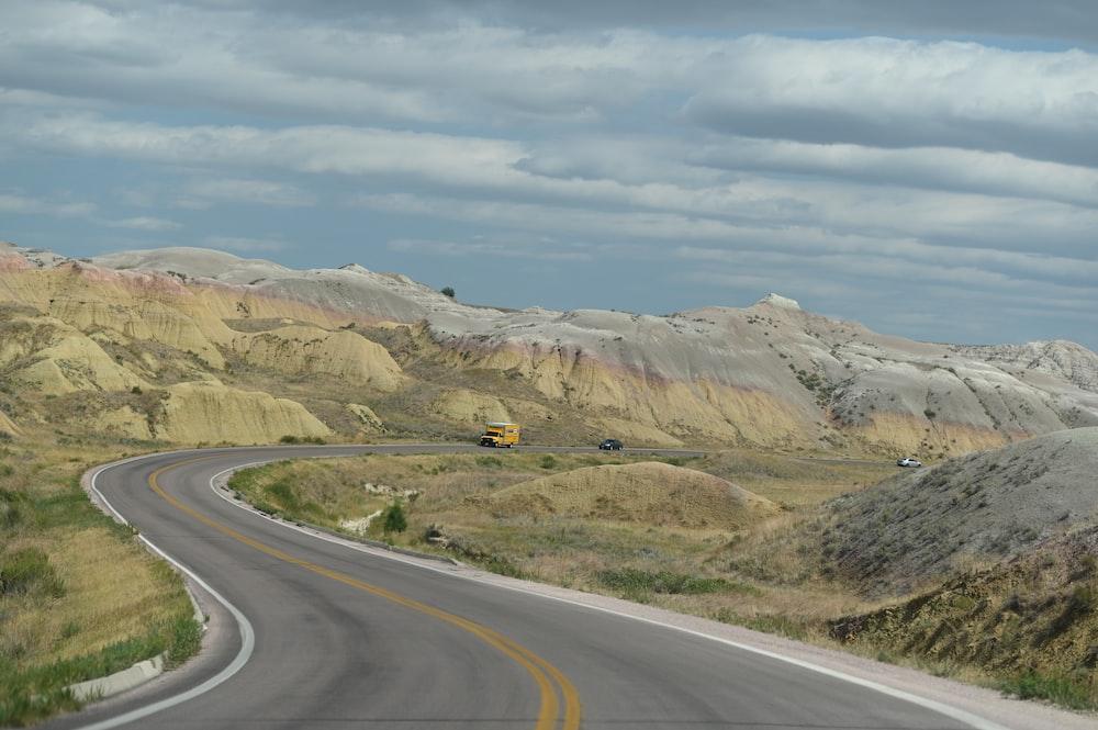 gray asphalt road near brown mountain under white clouds during daytime