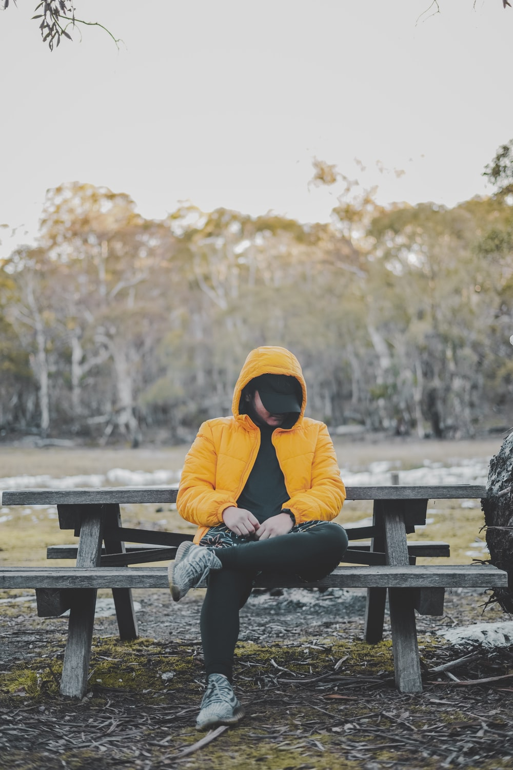 woman in yellow hoodie sitting on brown wooden bench during daytime