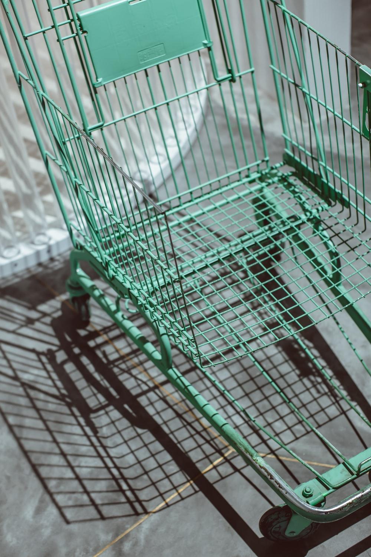 green metal shopping cart on white floor tiles