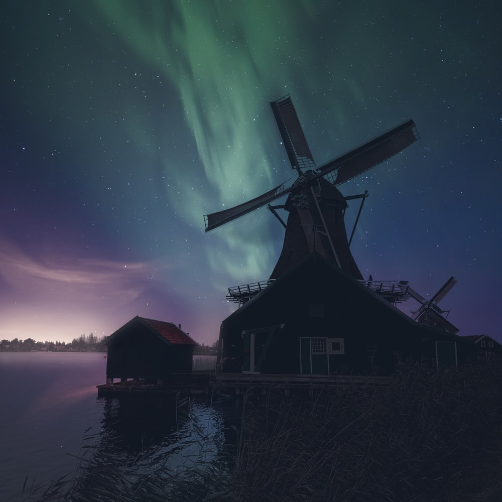 silhouette of house near body of water during night time