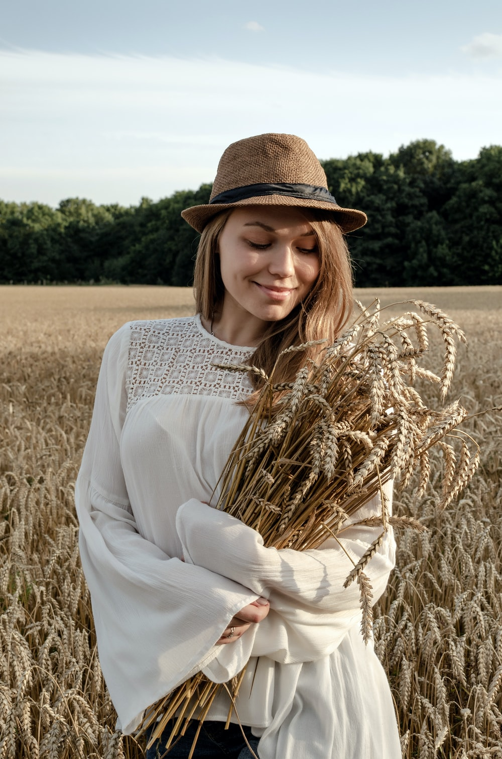 woman in white long sleeve shirt and brown hat standing on brown wheat field during daytime