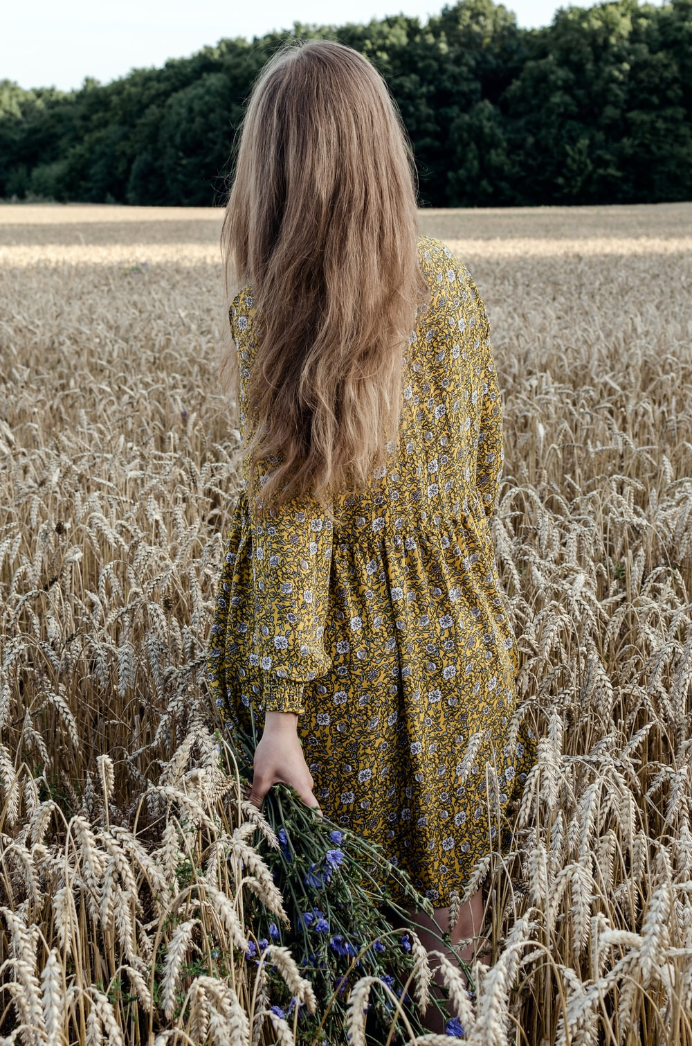 woman in yellow and black dress standing on brown grass field during daytime