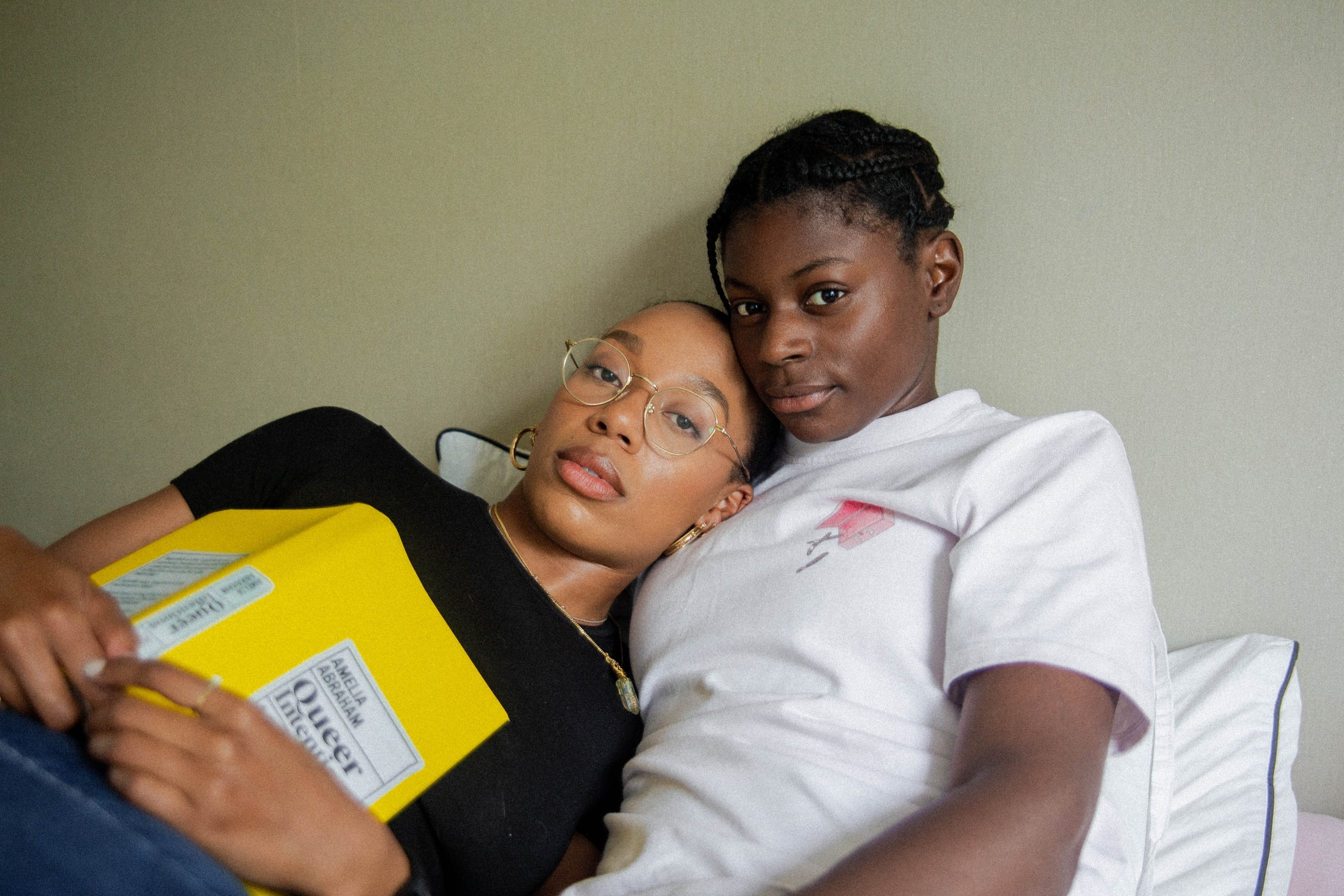 a queer couple in bed looking at camera, one is holding a yellow queer book