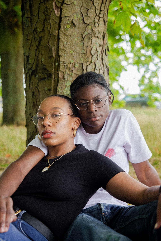 woman in black t-shirt wearing eyeglasses sitting with woman in white t-shirt wearing eyeglasses
