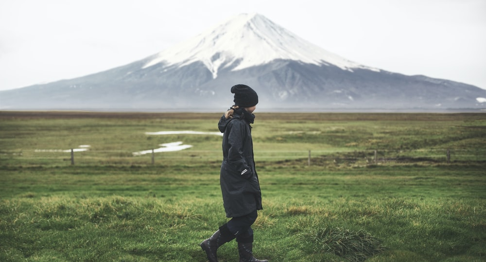 man in black jacket standing on green grass field near snow covered mountain during daytime