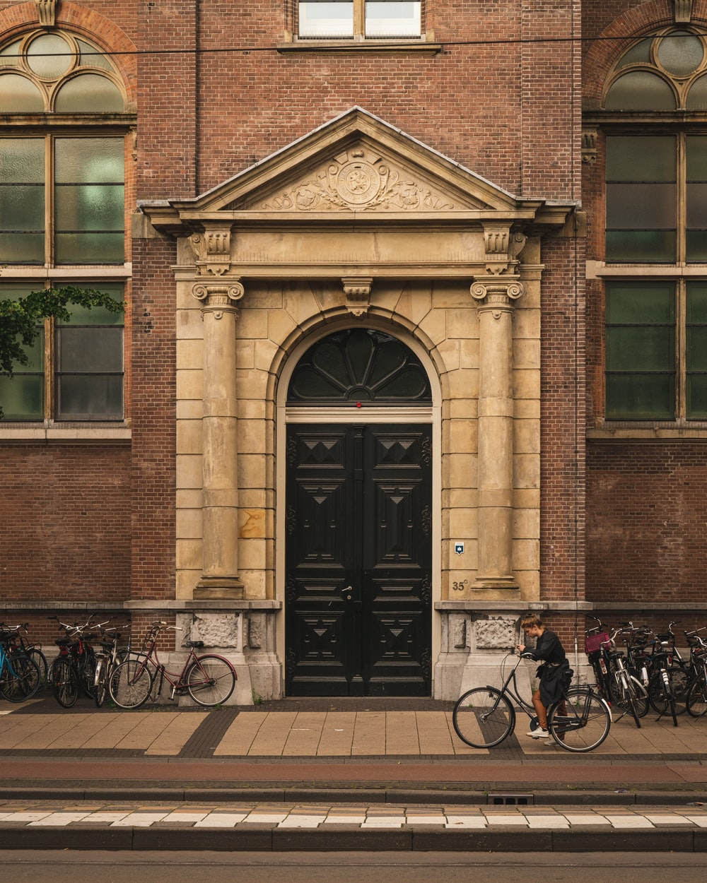 black bicycle parked beside brown concrete building during daytime