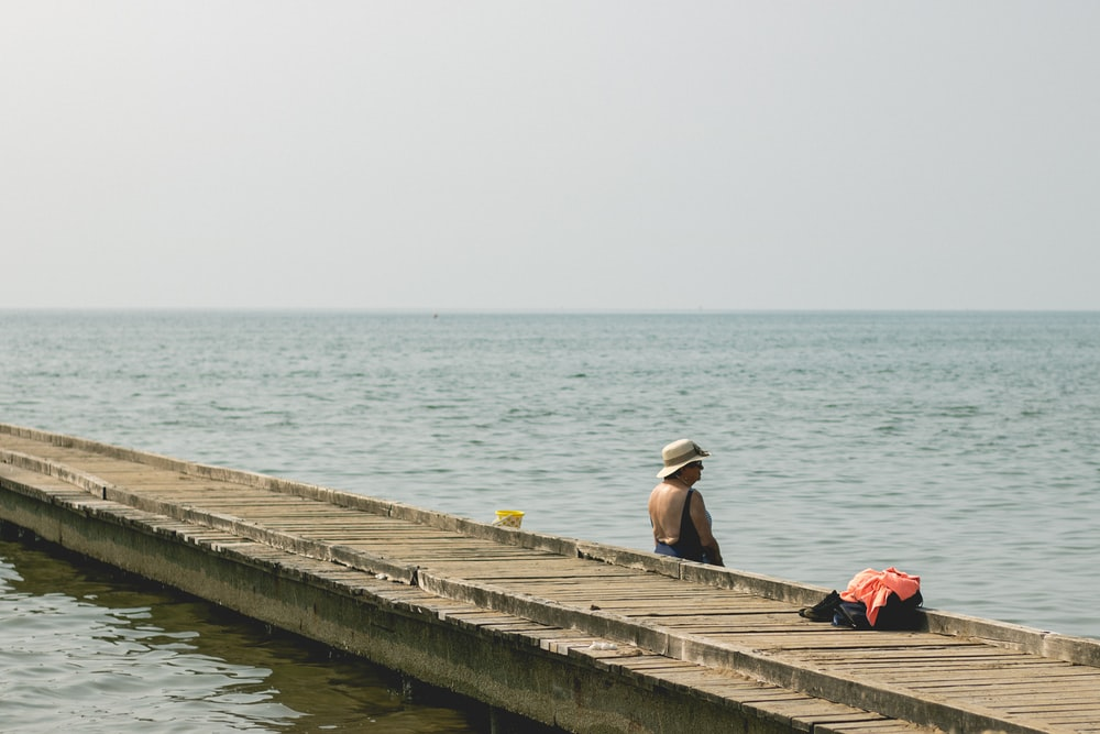 man and woman sitting on wooden dock during daytime