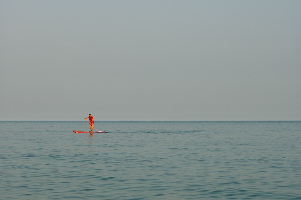 person in red shorts on body of water during daytime