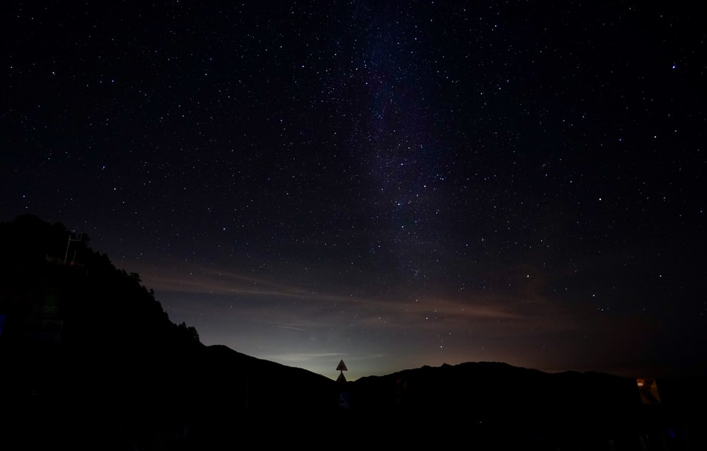 silhouette of person standing on hill under starry night