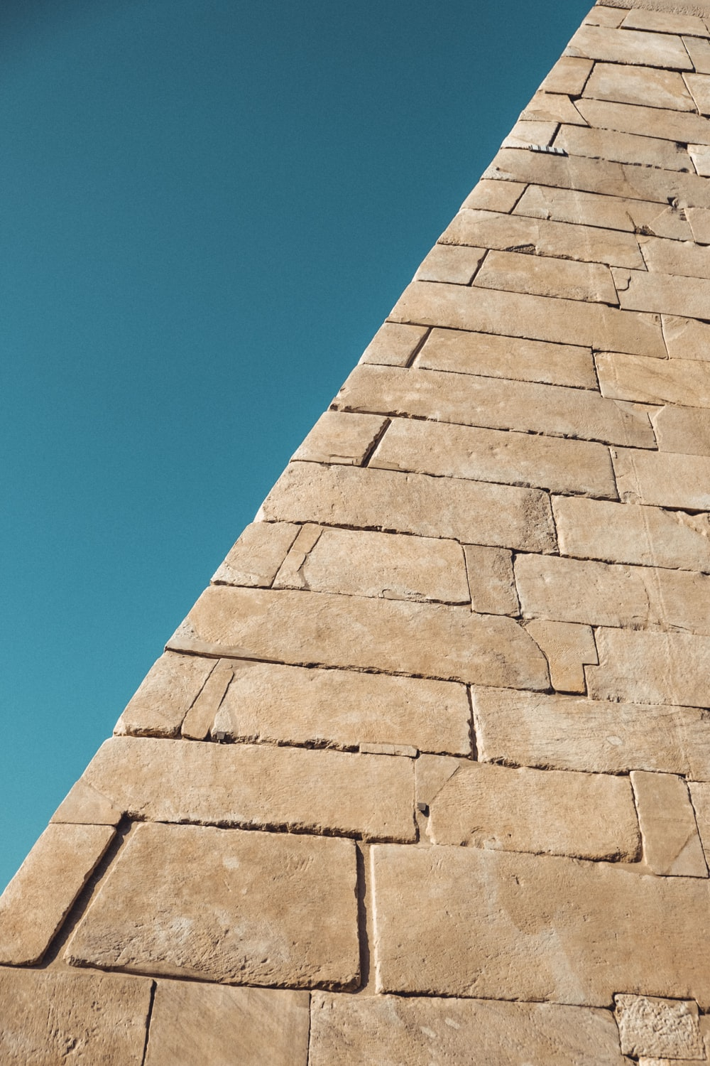 brown brick wall under blue sky during daytime