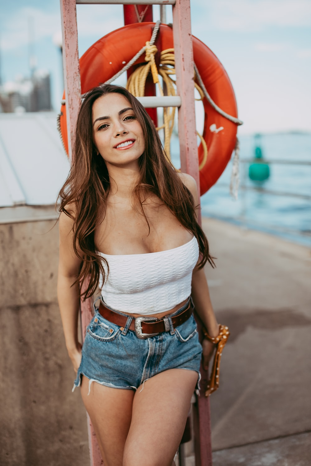 woman in white tank top and blue denim shorts standing near red metal railings during daytime