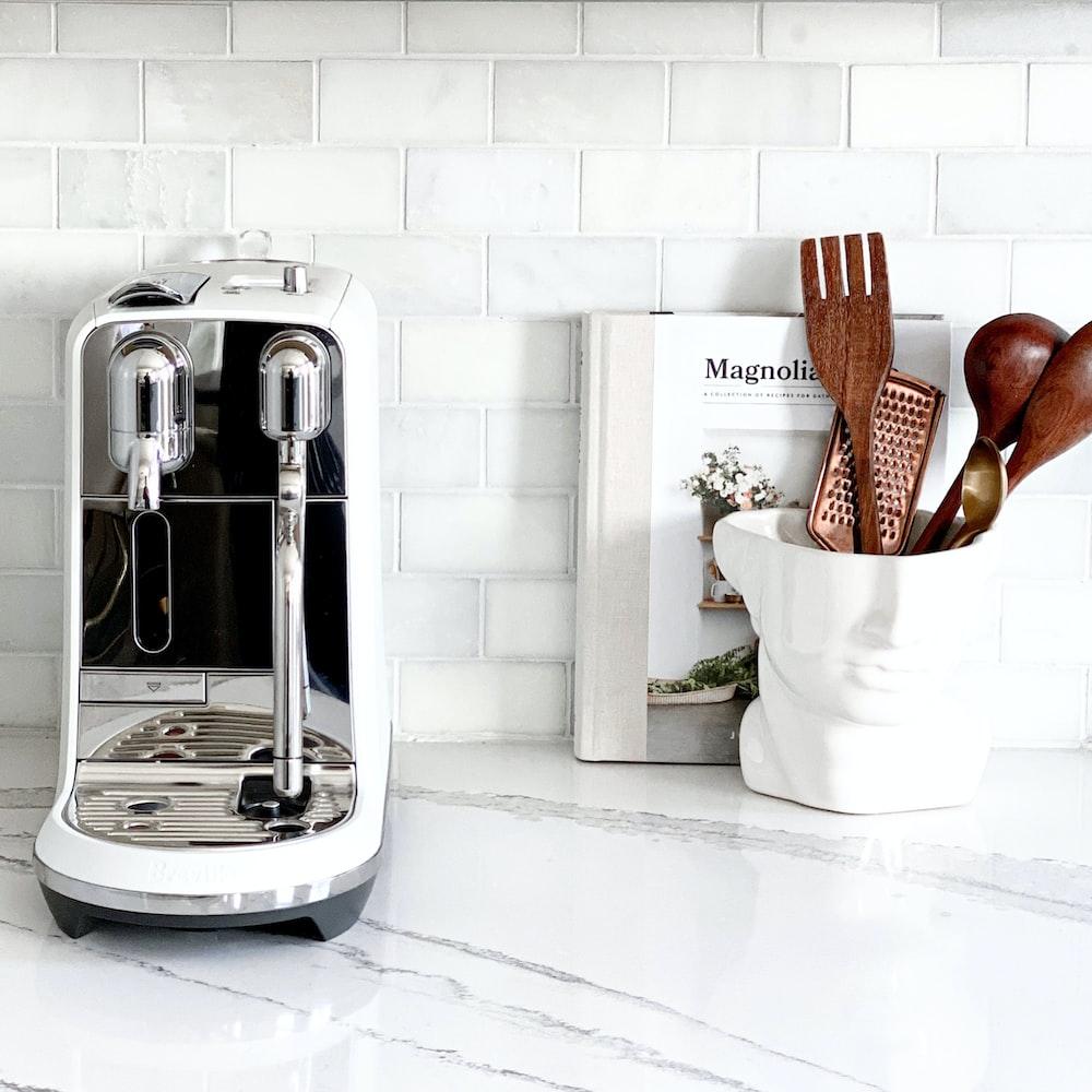 white and silver coffee maker beside white ceramic mug