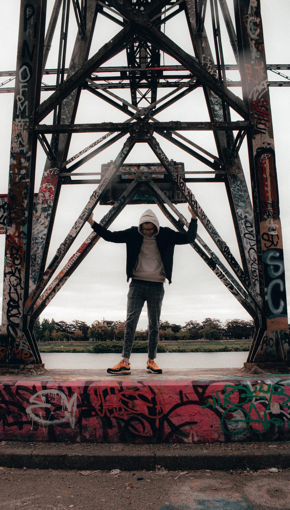 man in black jacket standing on brown wooden bridge