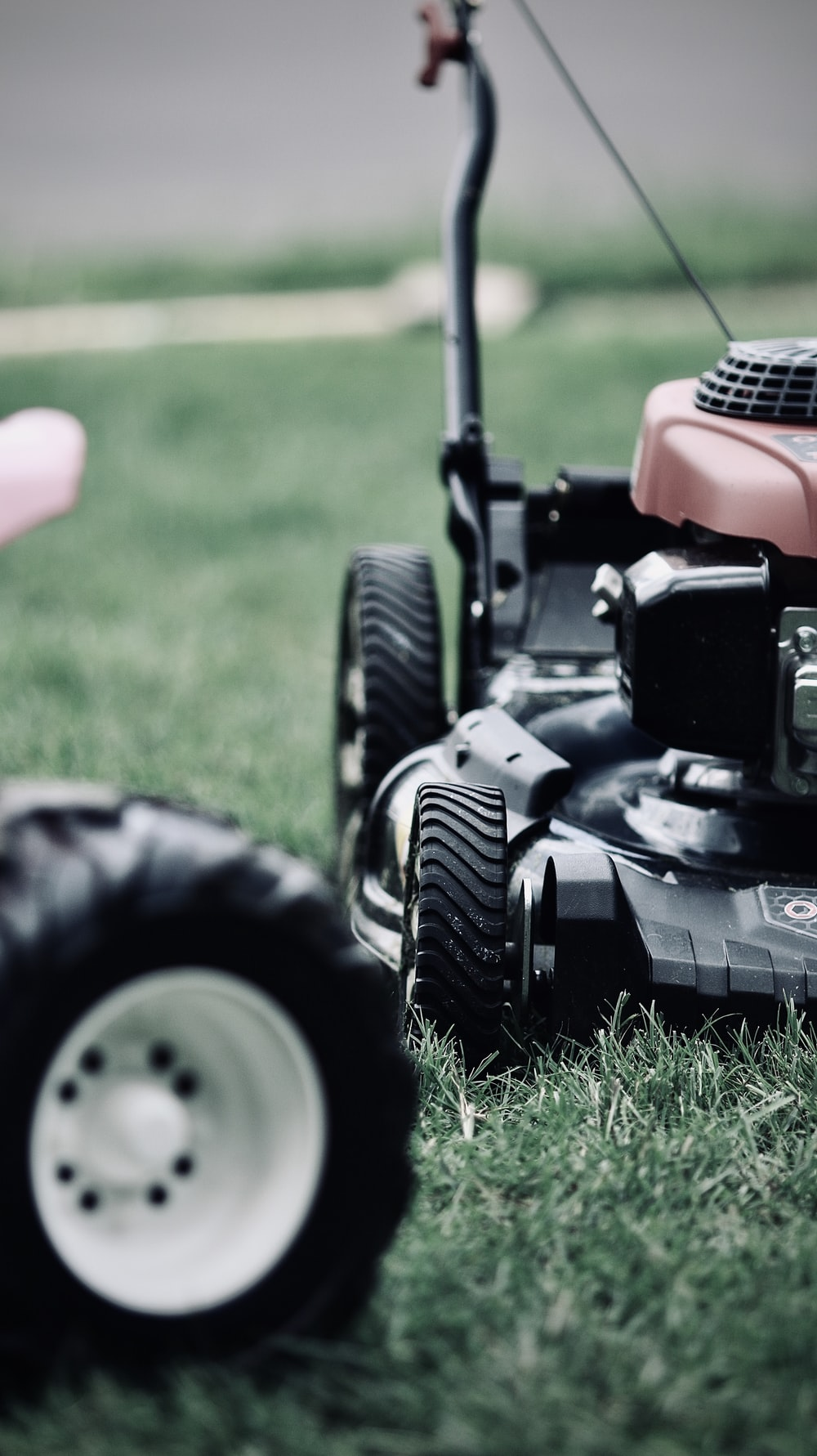 black and red ride on lawn mower on green grass field during daytime