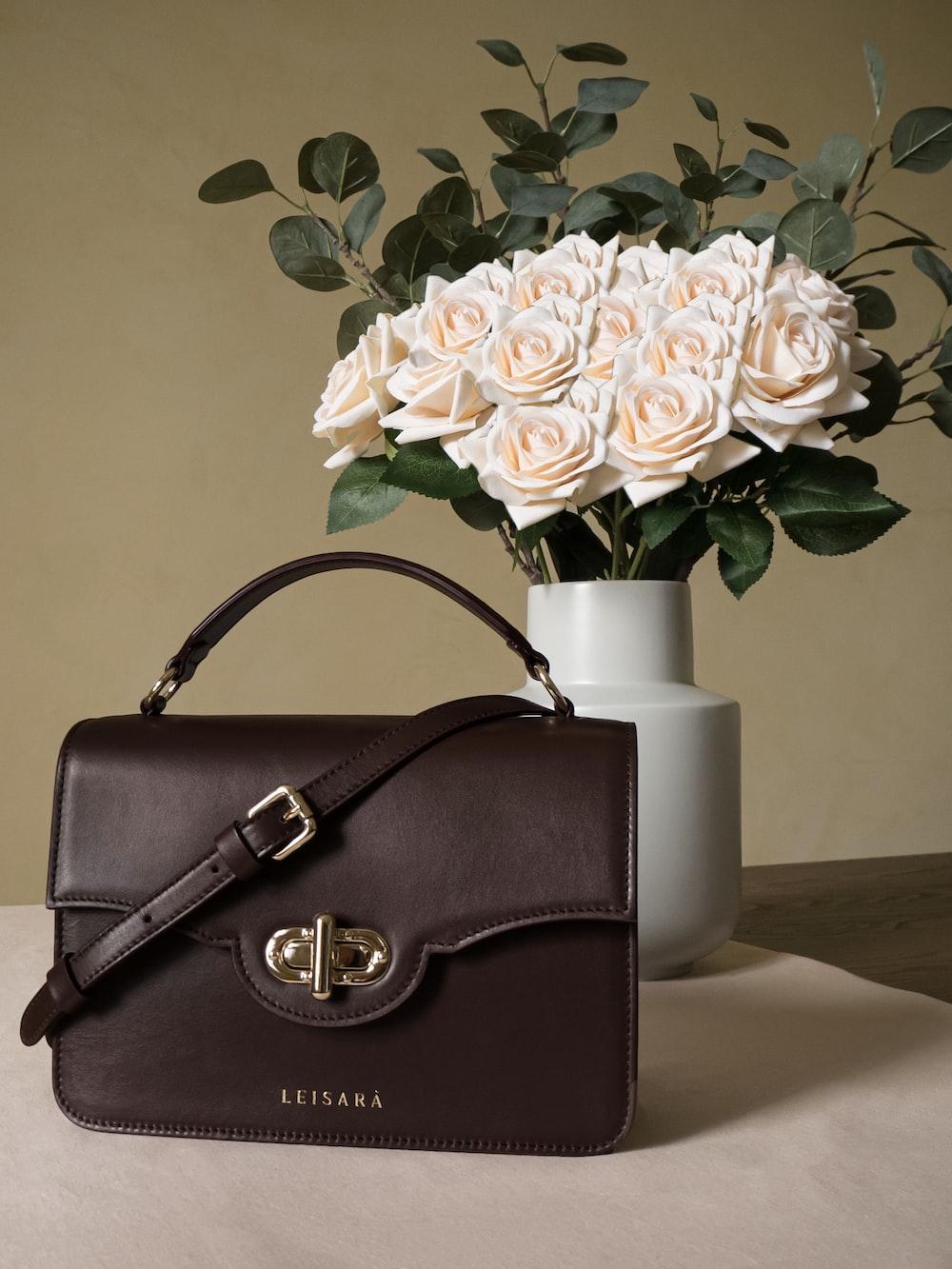 brown leather handbag beside white flower vase