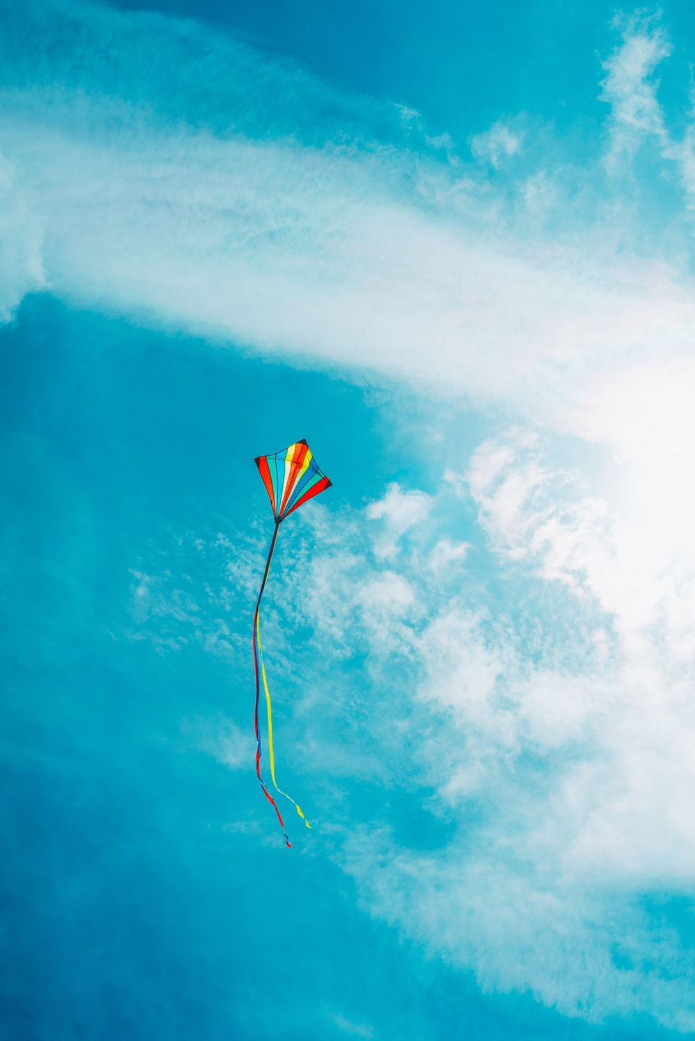 red and yellow kite flying under blue sky during daytime