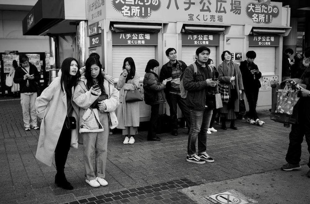 grayscale photo of 3 women standing on sidewalk