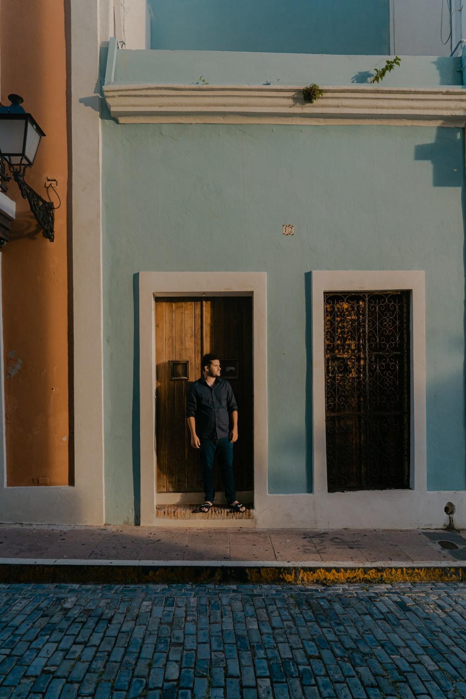 man in black jacket standing beside blue wooden door