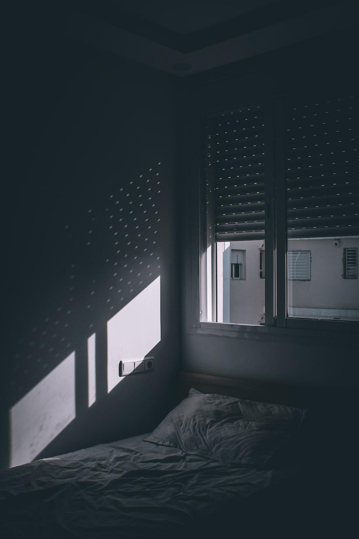grayscale photo of bed near window