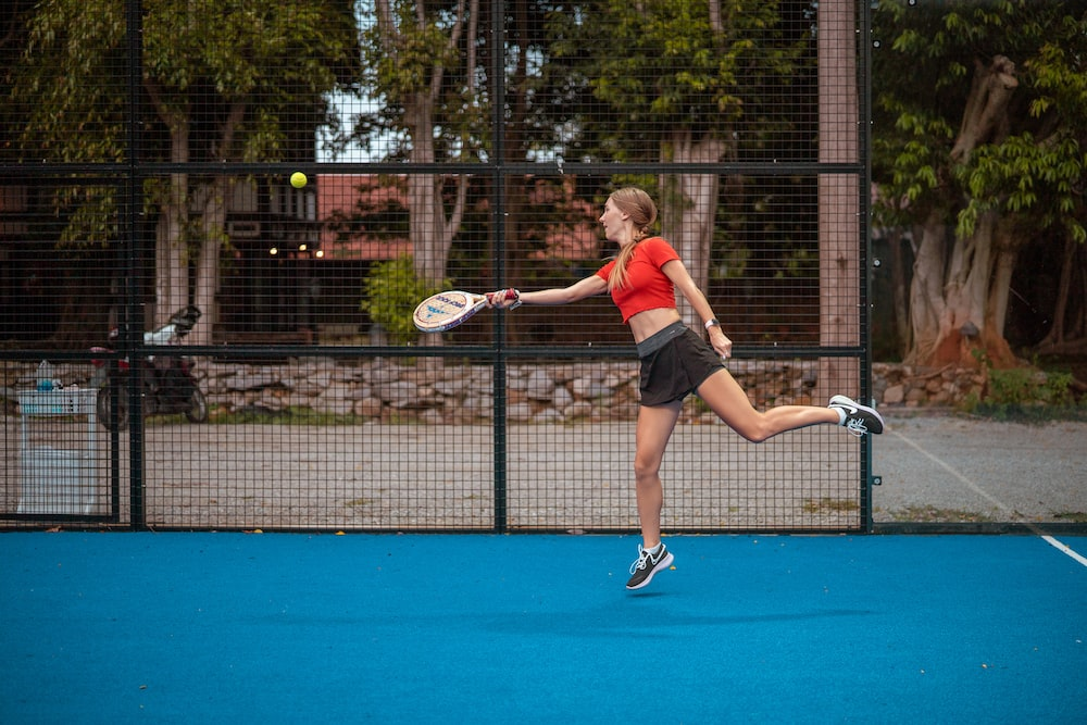 woman in red tank top and black shorts holding tennis racket