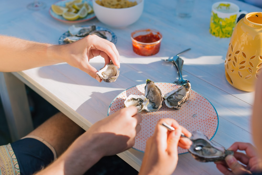 person holding a silver fish on a table