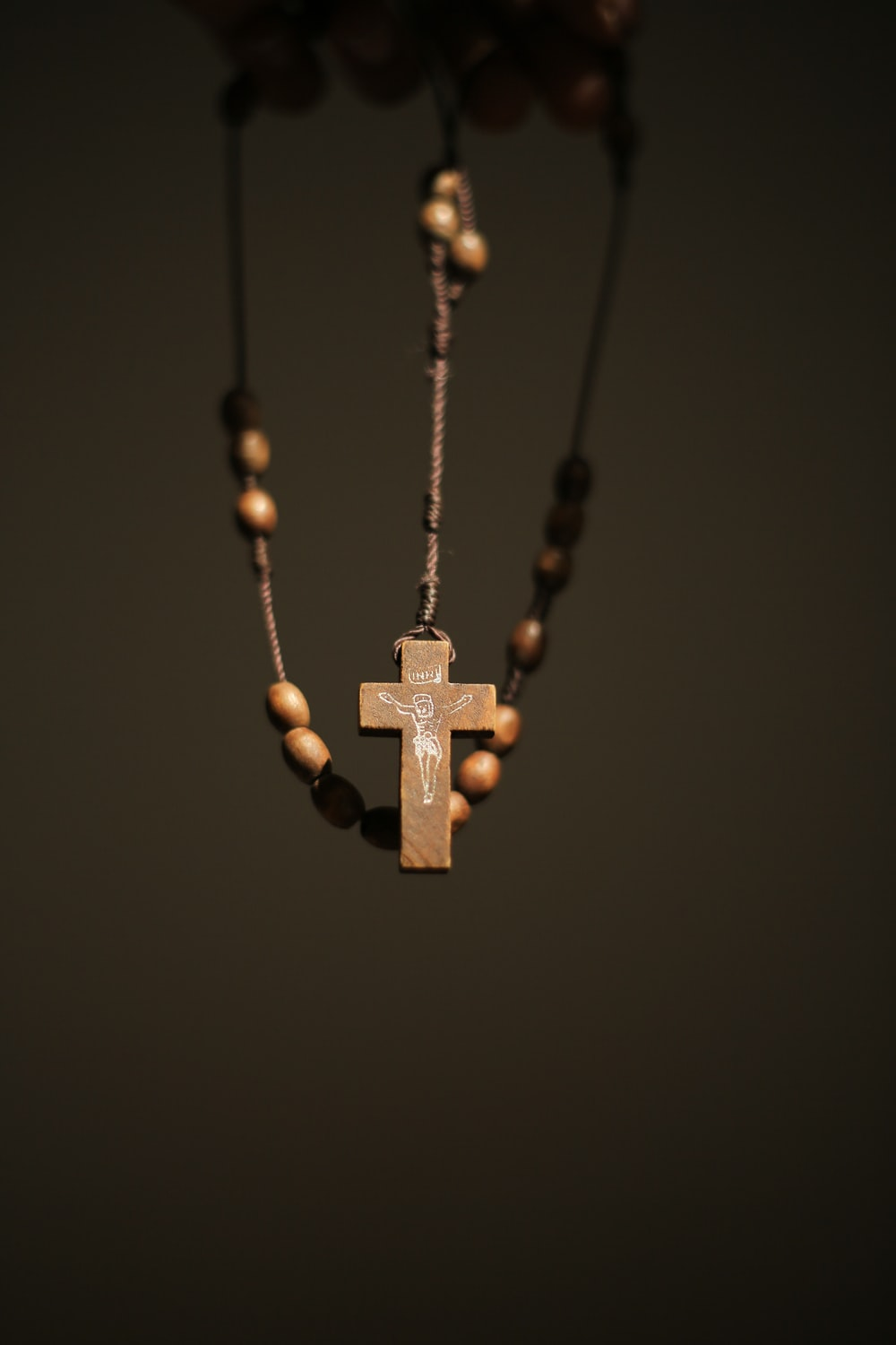 gold cross pendant necklace on black background