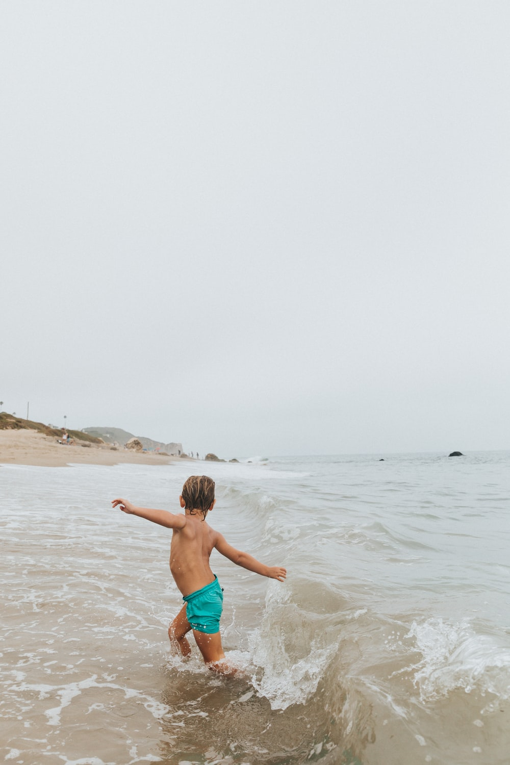 girl in blue shorts running on beach during daytime