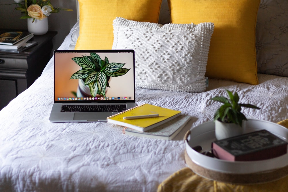 macbook pro on white bed