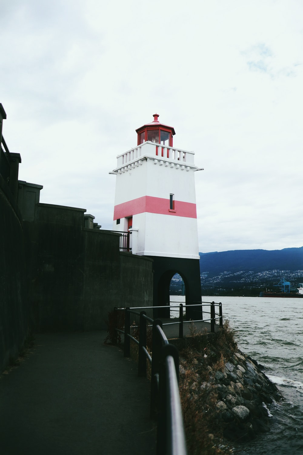 red and white concrete lighthouse near body of water during daytime