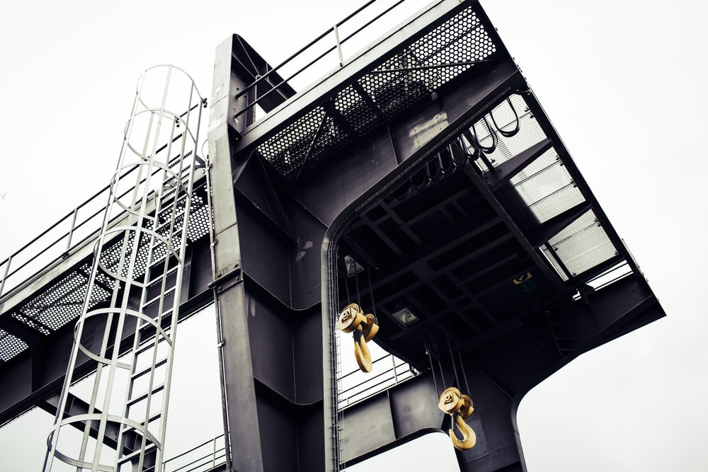 man in yellow shirt and black pants jumping on black building