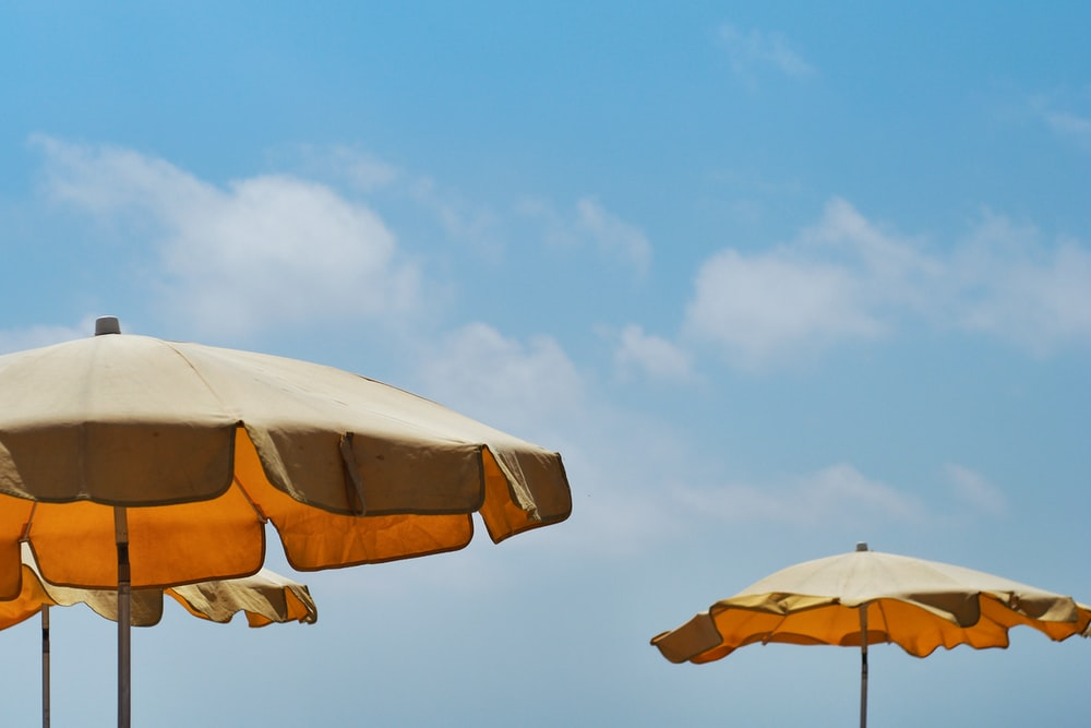 white and yellow umbrella under blue sky during daytime