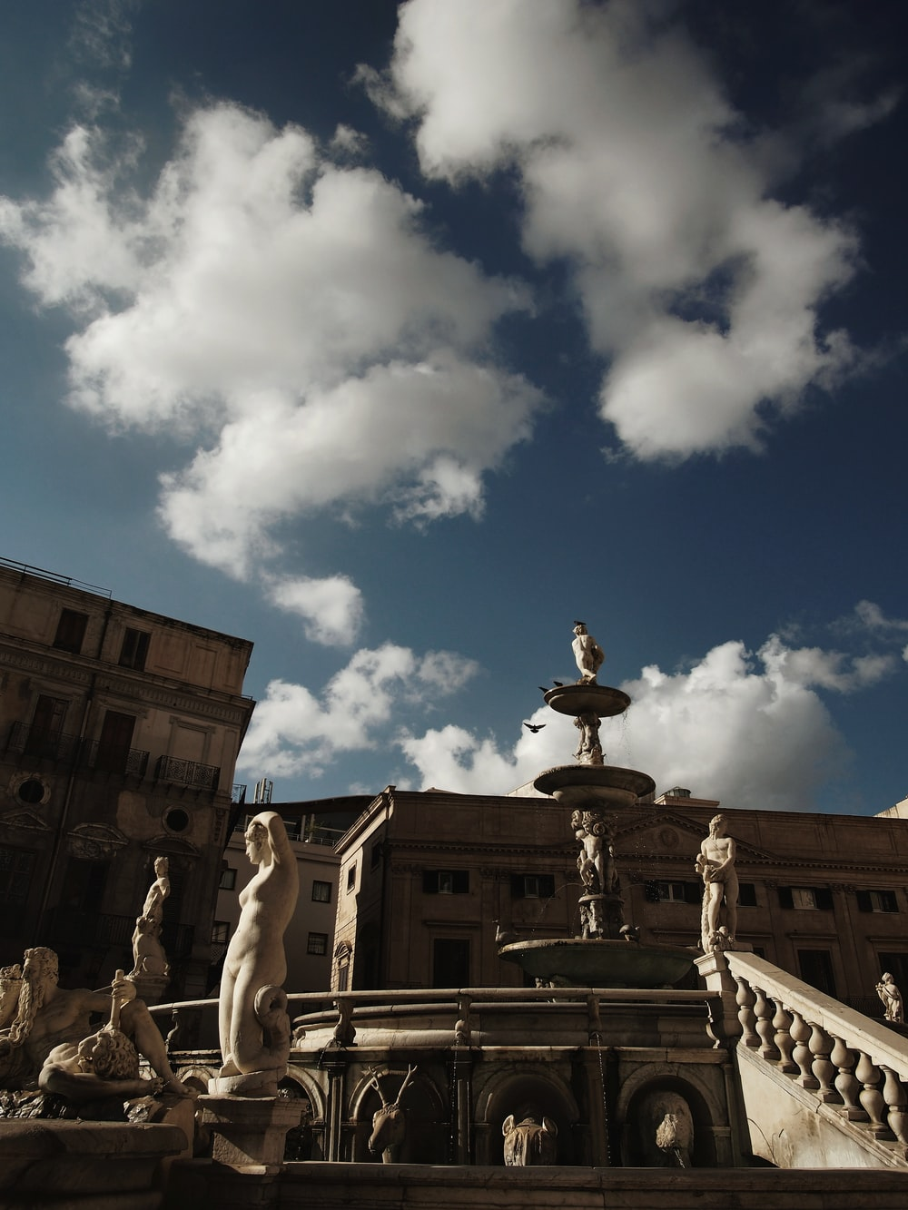 statue of people under blue sky and white clouds during daytime