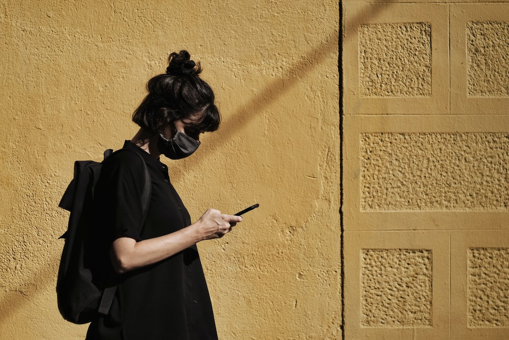 woman in black dress holding smartphone