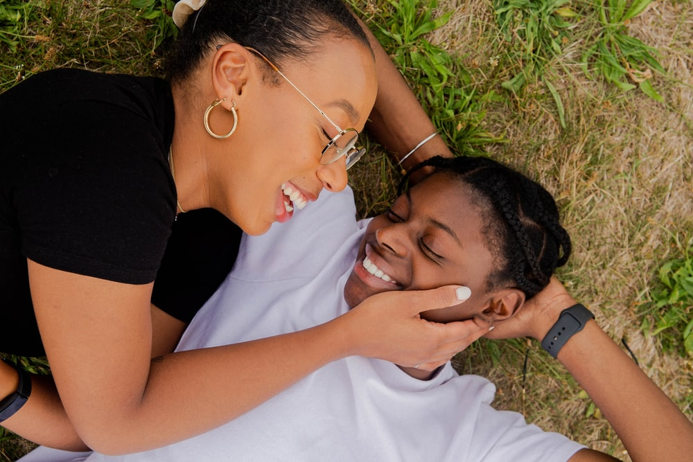 woman and woman kissing on green grass field during daytime