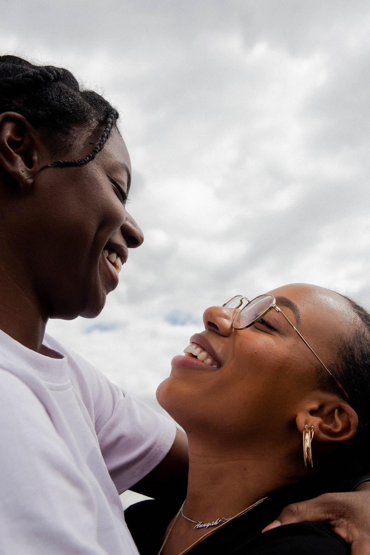 two women smiling during daytime