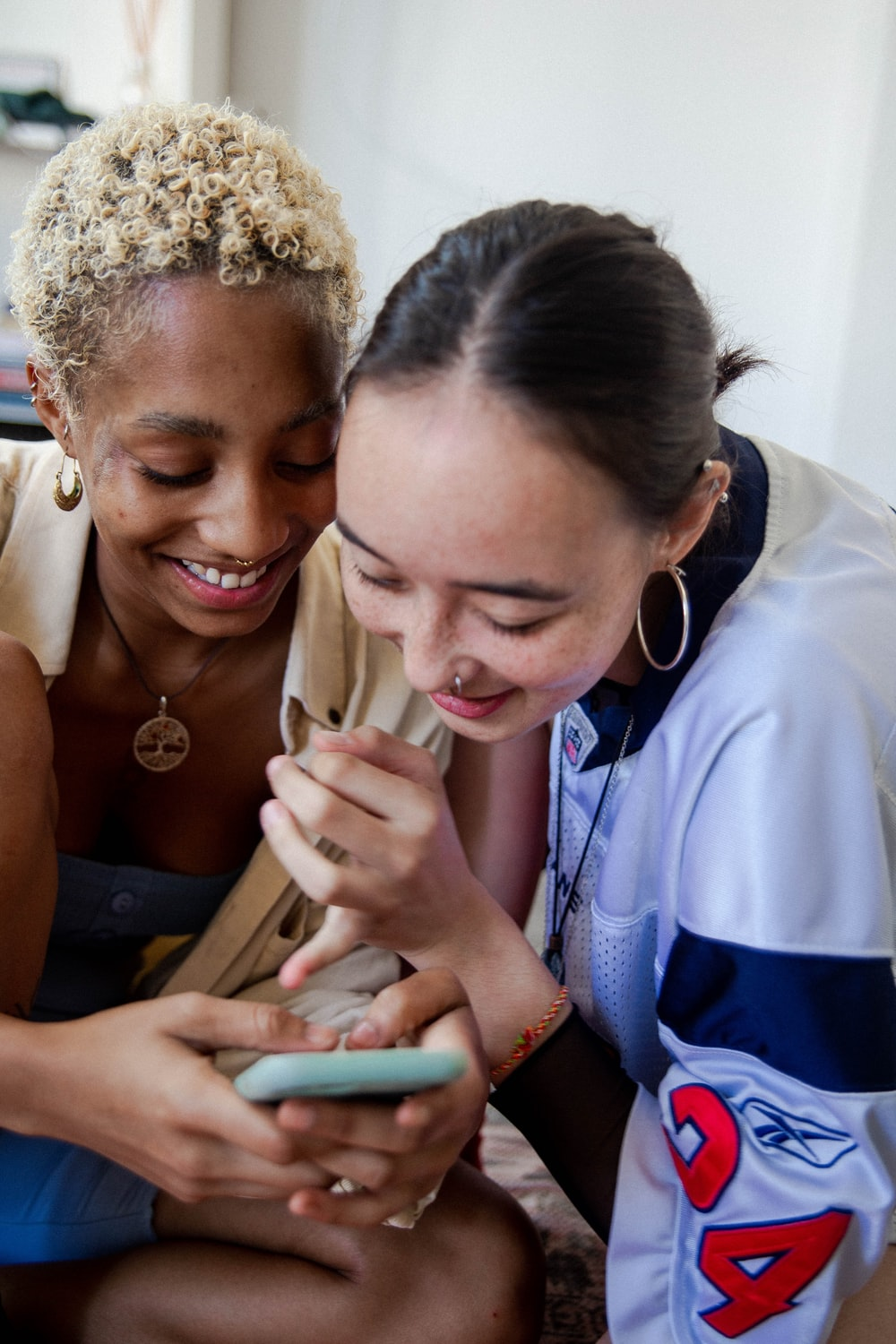 two women laughing and holding a smartphone