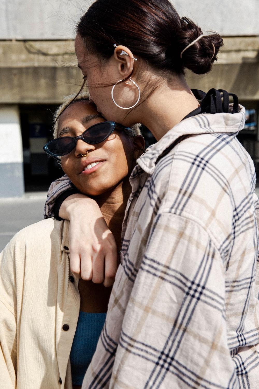woman in plaid shirt hugging woman in brown shirt