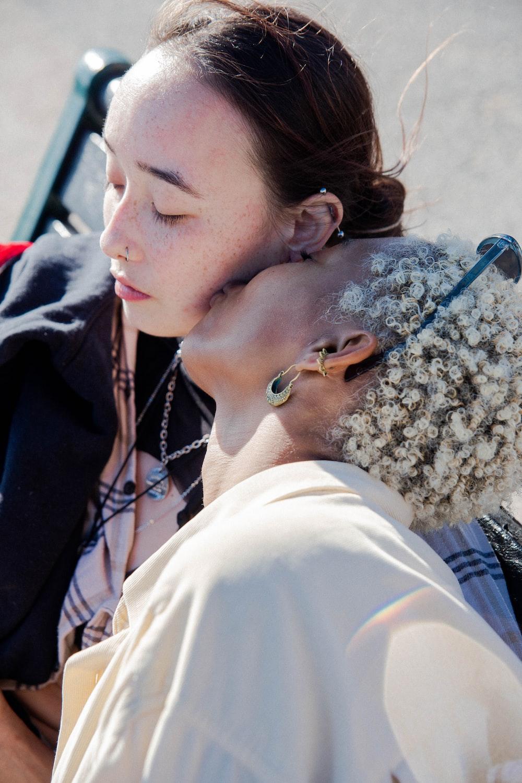 woman in white shirt kissing woman in black shirt