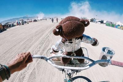 man in brown knit cap riding bicycle on brown sand during daytime burning man teams background