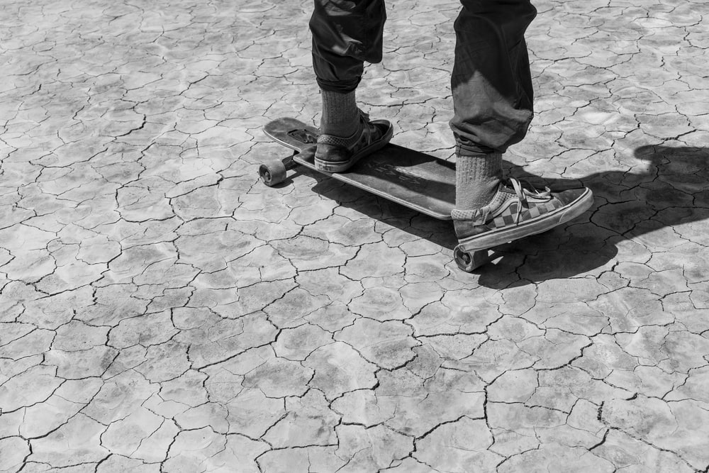 grayscale photo of 2 children standing on concrete floor