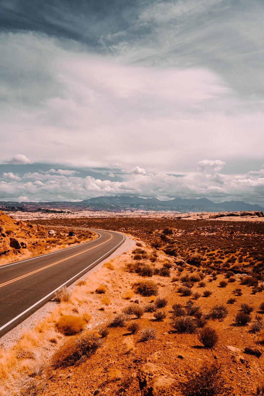 gray asphalt road under white clouds during daytime