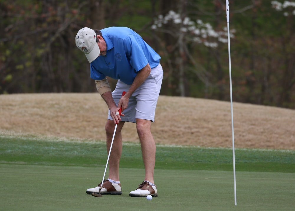 man in blue shirt and white shorts playing golf during daytime