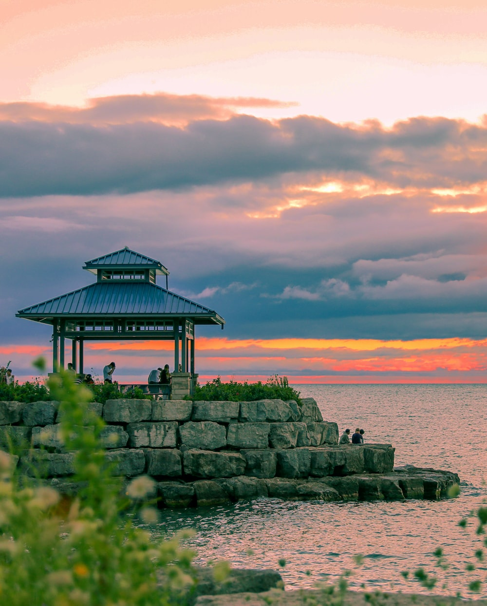 brown wooden gazebo on gray rock formation near body of water during daytime