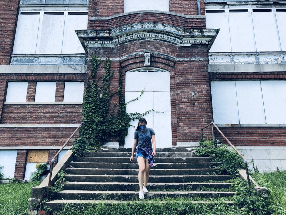 woman in black shirt and blue denim shorts standing on stairs