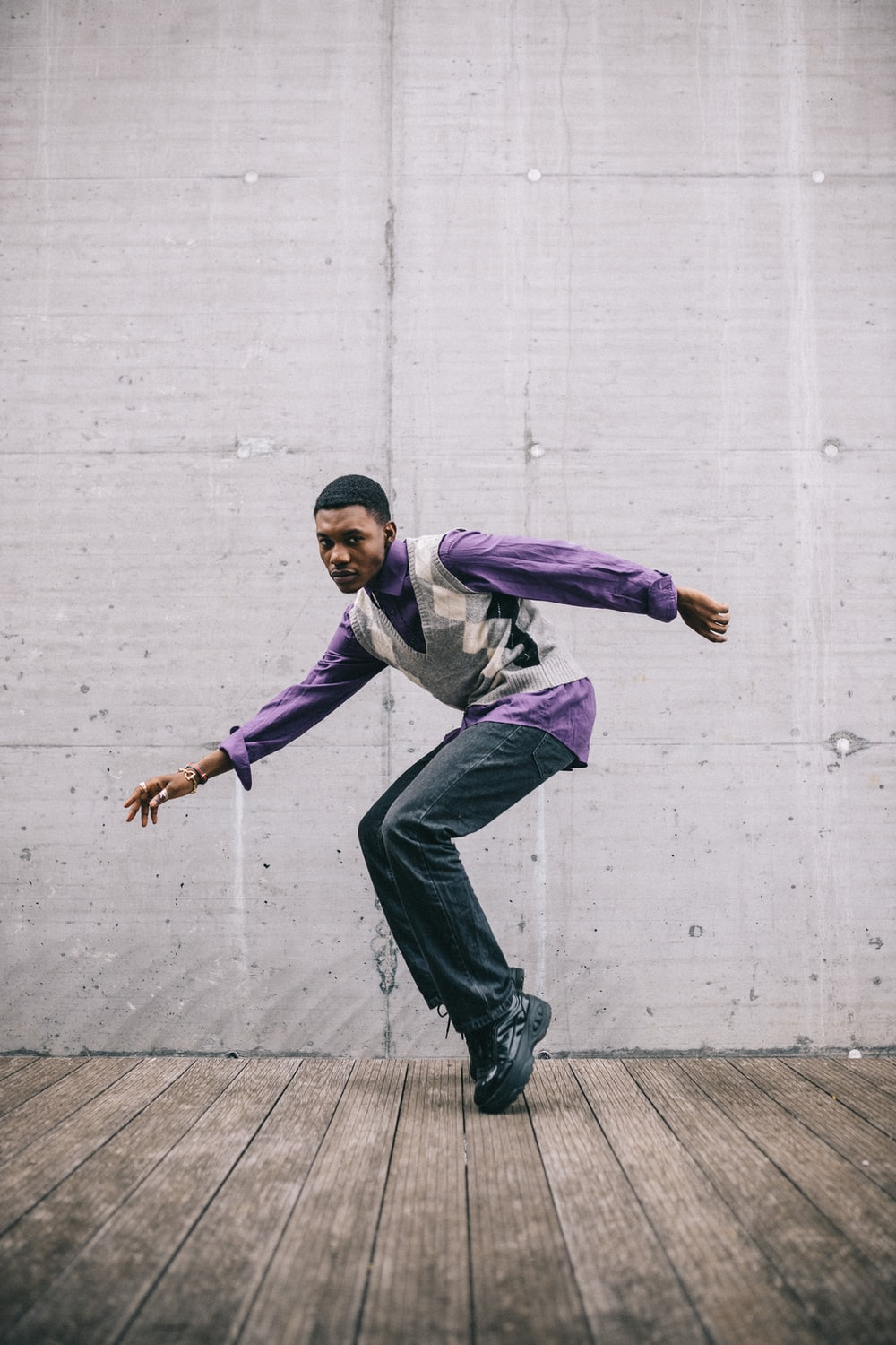 man in purple dress shirt and black pants jumping on gray concrete floor during daytime