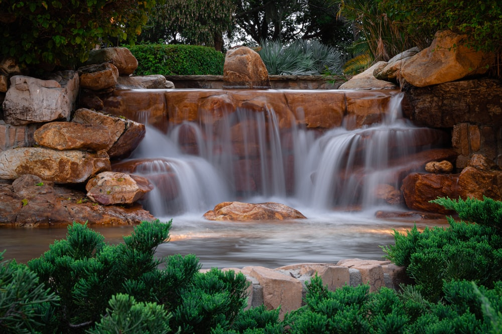 water falls with green plants