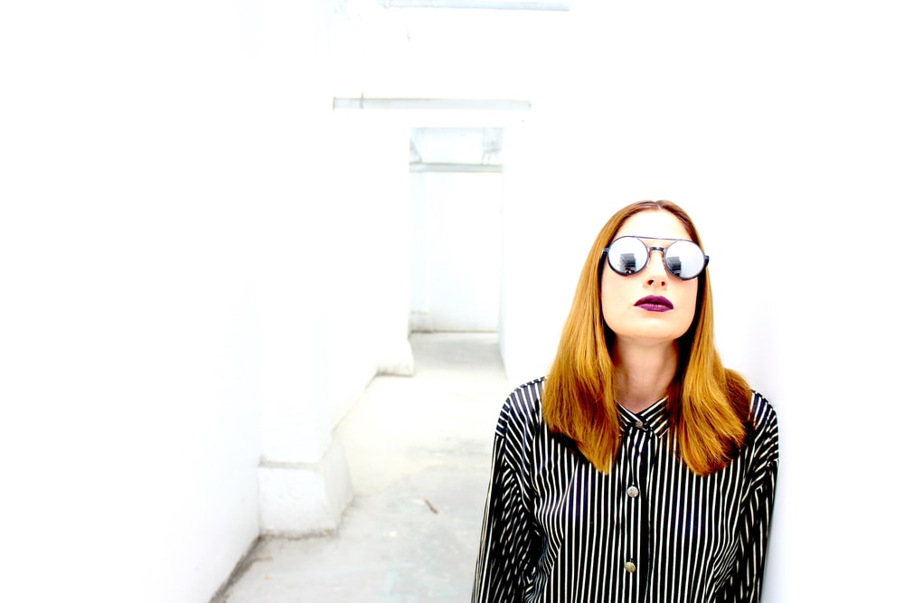 woman in black and white striped long sleeve shirt wearing brown sunglasses