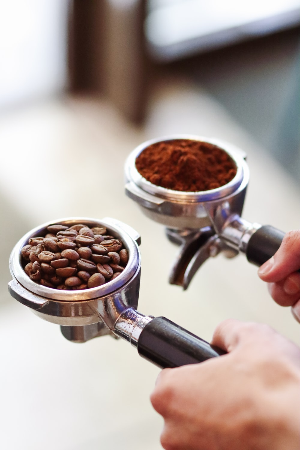 person pouring coffee on coffee beans in white ceramic mug